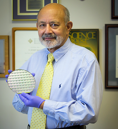 Photograph of Jay Baliga, who developed the PRESiCE process holding a wafer of silicon carbide devices.