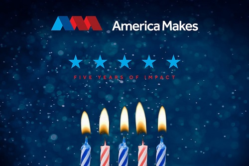 "Photograph of people standing in front of an image of 5 candles and the text ""Five years of impact.  America Makes."