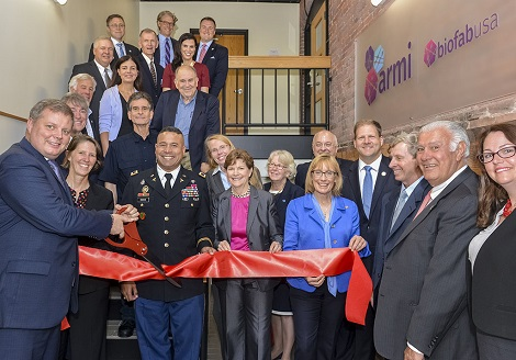 Photograph of members of the Board of Directors and Stakeholders Council for BioFabUSA holding and cutting a large red ribbon.